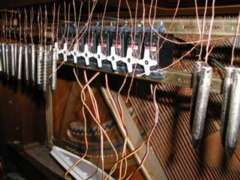 Photo of solenoides beneath the keyboard of a piano